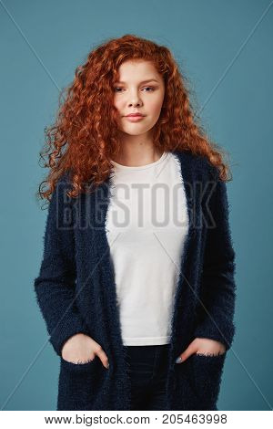 Portrait of beautiful ginger student girl with wavy hair and freckles holding hands in pockets, looking in camera with satisfied look. Vertical shot