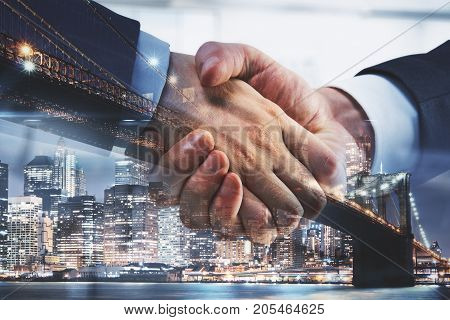 Side view and close up of professional handshake on abstract modern downtown city background. Teamwork concept. Double exposure
