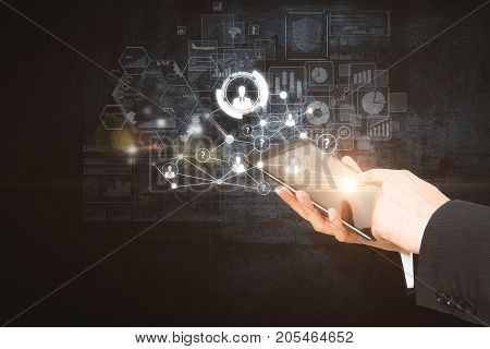 Side view and close up of businessman hands using tablet with digital business hologram on dark background. Device and innovation concept. Double exposure