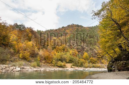 silent, perfection of nature, season concept. at the foot of rocky hills with autumn forests of fire colour there is stony bank and calm river with lazy green waters