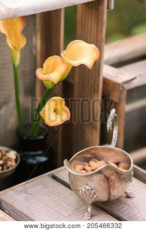 style, decoration, food concept. beautiful and elegant flowers of delicate orange colour that called arum lilies, placed in the jar with dark glass nearby with interesting silver dish full of nuts