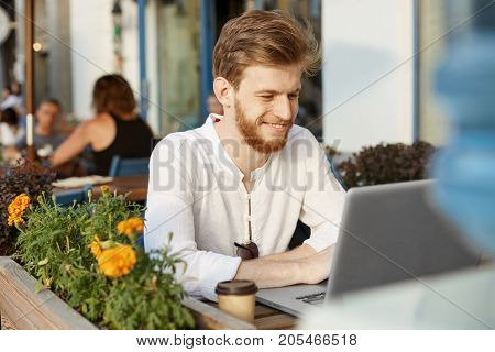 Mature attractive red-head bearded guy in fashionable white shirt looking in his notebook, being glad about big profits from his startup project