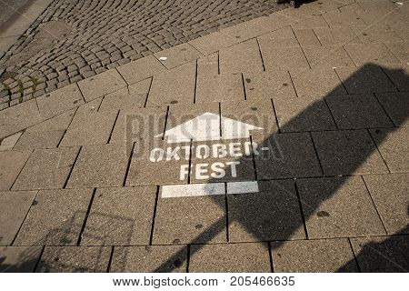 Sign painted on a sidewalk indicating the way to the Oktoberfest for visitors