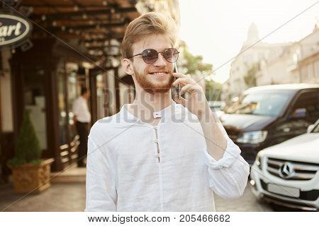 Beautiful young ginger man in sunglasses and white shirt brightfully smiling, talking on phone while walking down city streets. Lifestyle concept