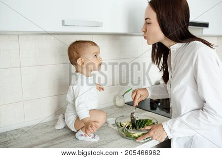 Young beautiful mother cooking salad for breakfast and trying to kiss her little son while he looking at mom with interested expression