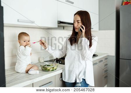 Tired young mother talking on phone in kitchen and trying to feed son with salad while he looking aside and refusing to eat