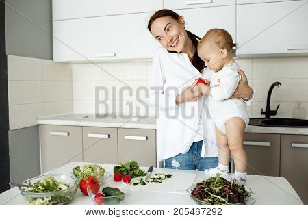 Attractive mother with dark hair cooking dinner and talking on phone with husband while little son standing on table and eating tomato from mother hands