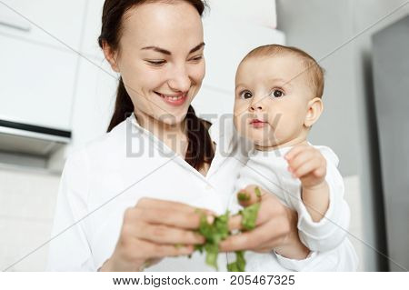 CLose up of beautiful young mother holding her pretty little boy on hands and cooking salad for breakfast. Son looking aside not interested in mom's work