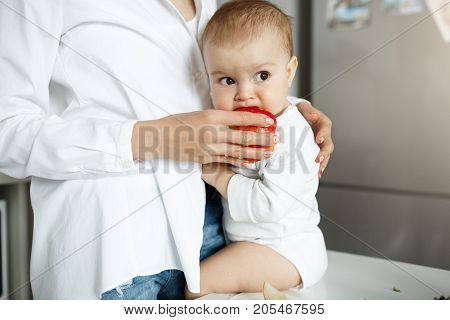 Close up portrait of innocent little baby boy sitting on table in kitchen, looking aside and eating red apple from mother hands