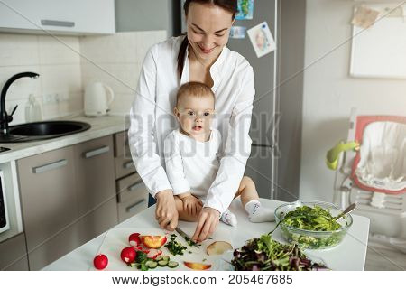 Portrait of happy young family of mother and newborn child spending time together in weekend morning cooking lunch for father