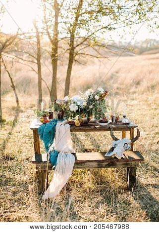 table setting, fall, travelling concept. on the wooden table for picnic standing in the field there is stunning bouquet of white flowers and cultery, decorative skull with horns placed on bench