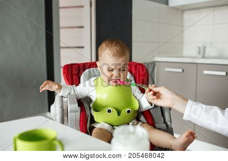 Portrait of unhappy newborn son in green bib crying and refusing to eat from the spoon while mother patiently trying to feed him