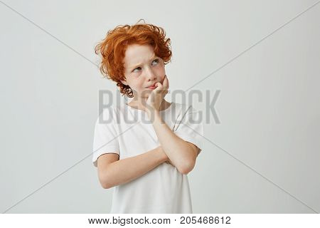 Close up portrait of little ginger boy with freckles thoughtfully looking aside remembering if he turns off iron before school