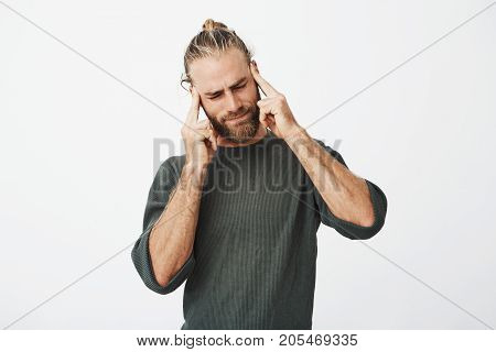 Beautiful nordic man with trendy haircut and beard being tired, massaging temples with fingers trying to concentrate on work