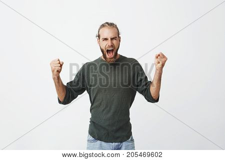 Happy attractive man with beard screaming loudly and expressive gesticulating with hands when his favourite football team finally won in match