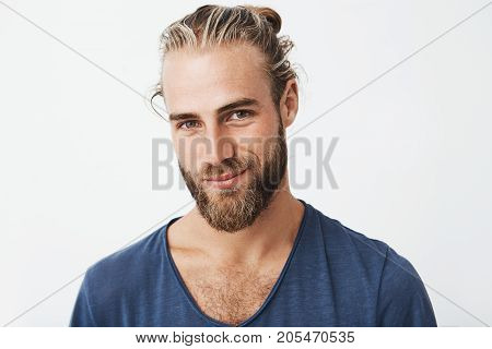Handsome swedish mature guy with great hairstyle and beard smiling, looking in camera with confident and flirty expression