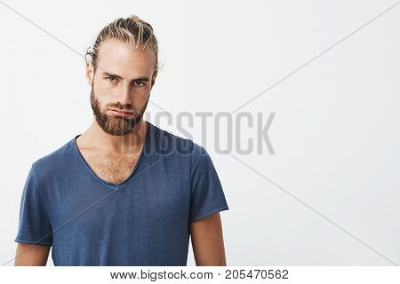Close up of unhappy handsome bearded guy curving lips and looking in camera upset with nobody gave him present for a birthday