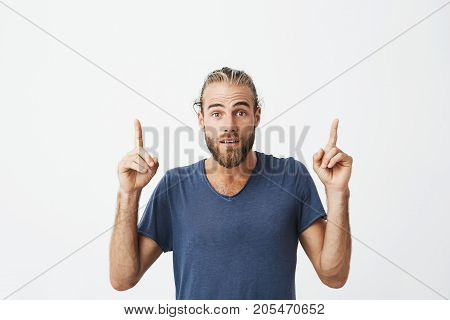 POrtrait og young handsome guy with fashionable hairstyle and beard pointing upside with fingers on free white background. Copy space