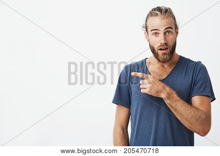 Close up of attractive swedish guy with good hair and beard looking in camera with surprised expression pointing at white wall. Copy space