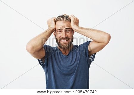 Close up of unhappy handsome guy with beard holding hair with hands, being super disappointed about broken new smartphone
