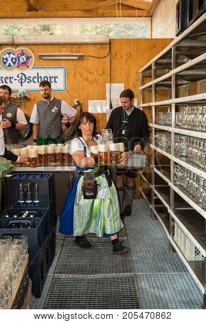 MunichGermany-September 242017: A waitress rushes out freshly draught beer from a serving station at the Oktoberfest