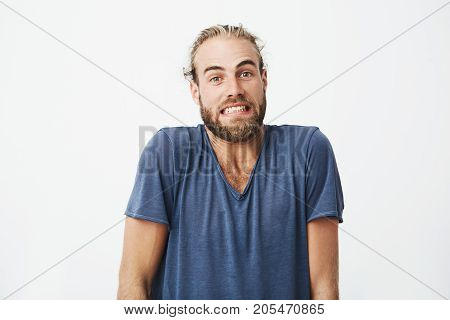 Portrait of beautiful bearded guy with trendy haircut funny posing for article university newspaper. Face expressions and emotions