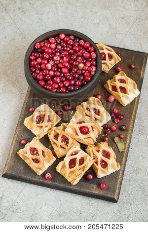 Sweet cranberry dessert.  Homemade cookies with a jam filling and fresh ripe cranberries in a round wooden bowl on a cutting board.