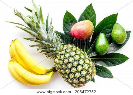 Tropical fruits background. Mango near exotic leaf, banana and pineapple on white top view.