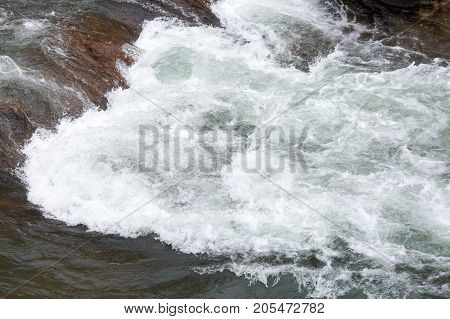 water resources, rafting, travelling concept. rough waters of river are creating underwater swirls in the dangerous stage of rapids with help of big stones and uneven surface