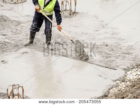 Construction worker manually prepares site for concreting