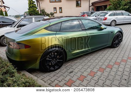 PRAGUE CZECH REPUBLIC - SEPTEMBER 23 2017. Tesla Model S gold and green color. The Tesla Model S in the colorful golden-green pearl design parks between the cars.