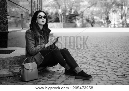 Brunette Girl Sitting On The Street With Cellphone, Black And White