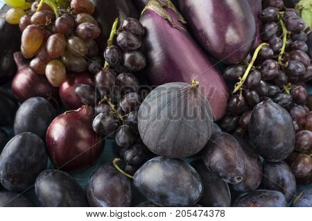 Purple food. Background of fruits and vegetables. Fresh figs plums eggplant and grapes. Top view