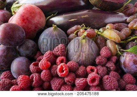 Purple food. Background of berries fruits and vegetables. Fresh figs plums apples raspberries beet eggplant and grapes. Top view