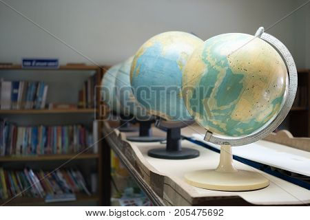Perspective of globe model simulation with bookshelf background in library room. Research and education concept