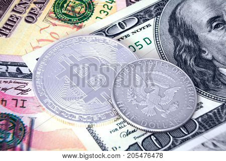 Silver bitcoin and 50 cent coin laying on dollar banknotes
