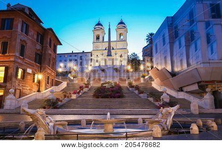 The Spanish Steps and Trinita dei Monti church in Rome, Italy, at dusk.