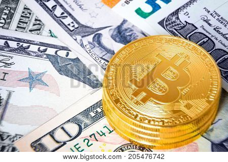 Stack of golden bitcoins on dollar banknotes