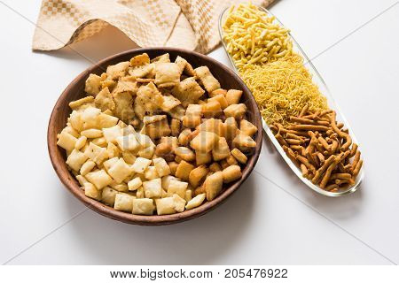 stock photo of Yellow Namkeen sev variety with shakkar para or shankar pale, Shakkarpare, Shakarpali served in white bowls arranged artistically, selective focus