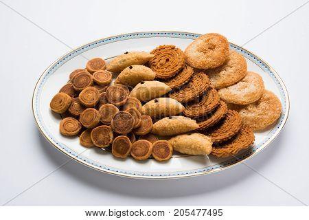 stock photo of Indian festival or diwali food called Bakarvad , karanji or Gujiya, Chakli or Murukku and Anarsa, selective focus