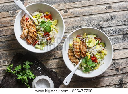 Pearl barley with seasonal garden vegetables and grilled chicken on wooden background top view. Healthy balanced food concept