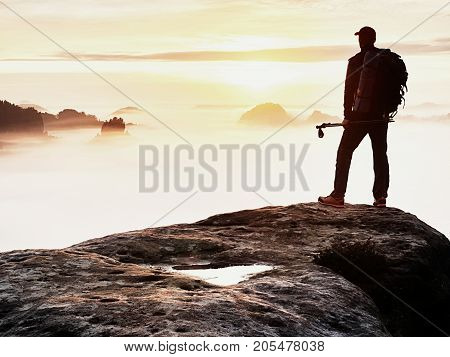 Man Silhouette With Poles In Hand. Sunny Spring Daybreak And Tourist Guide Stay On Sharp Cliff Of Mo