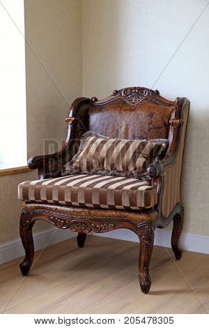 Vintage antique classic armchair in the room, leather brown armchair