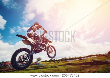 Racer on motorcycle participates and jumps. Close-up. concept of extreme motocross, sports racing. ray of light