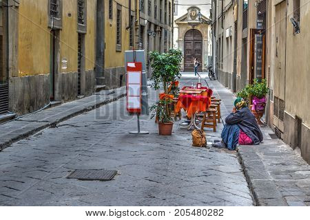 a homeless woman begging in the street