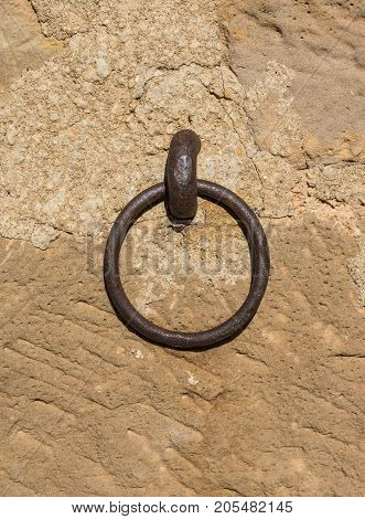 old iron ring a little rusty embedded in a stone wall, used to leave tethered animals like horses or mules