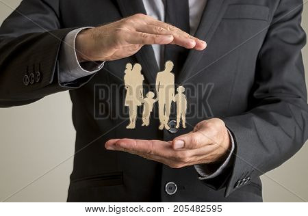 Businessman Protecting Family Silhouette With A Father Mother Baby And Two Children