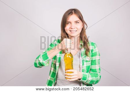 Young woman opens a bottle of beer. Concept of bad habits and alcoholism.