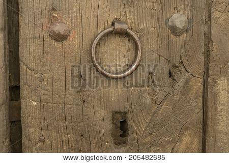 Closeup vintage door lock of external antique wooden door with a door knocker, weathered on a Country house