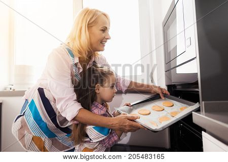 The girl and her grandmother make homemade cookies. Grandmother teaches her granddaughter. They load the biscuits into the oven